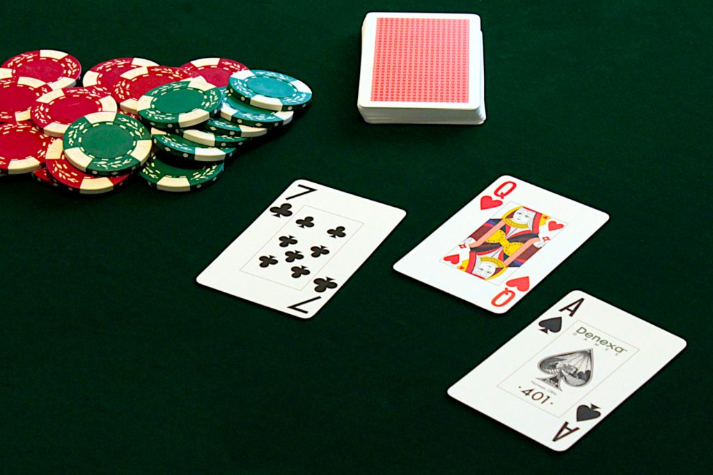 A game of In-Between in progress, showing a pile of red and green poker chips, a deck of cards, and three face-up cards: the queen of hearts between the seven of clubs and the ace of spades.