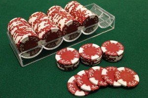 A rack of red poker chips, with a stack of twenty broken down in front of it.