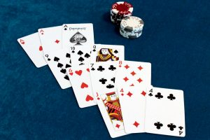Twelve playing cards, fanned out into four Brag hands.