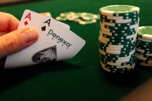 Two aces being held as hole cards by a player in a poker game.